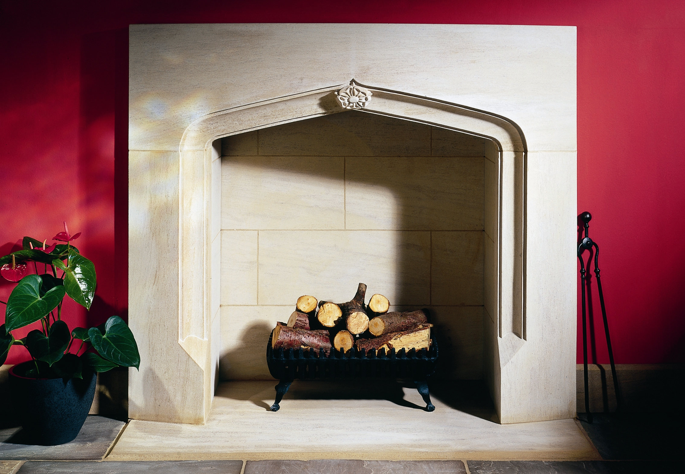 16. A modern interpretation of a Gothic fireplace in Ancaster Hard White stone, with carved rose detail – Derbyshire
